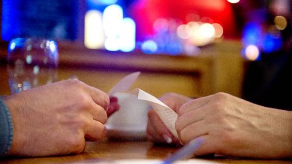 Två händer och kvitton på restaurangbord.