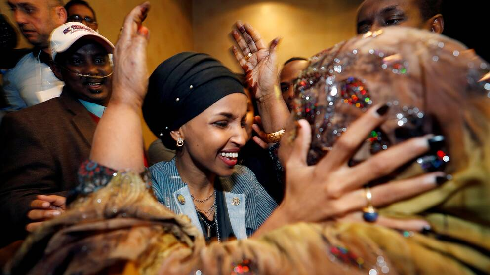 Ilhan Omar omfamnas av sin svärmor under nattens firande. Hon tar nu plats i representanthuset som första muslimska kvinna, tillsammans med Rashida Tlaib.