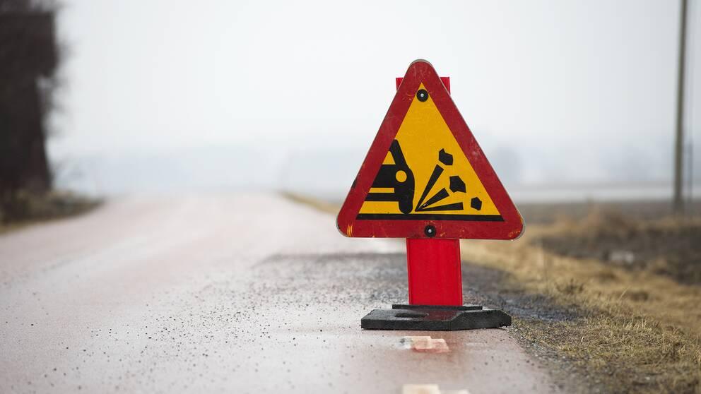 Ett tillfälligt vägmärke varnar för stenskott.