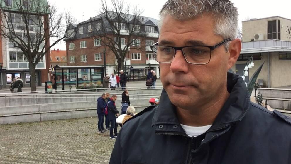 Jörgen Ivarsson från Falkenberg med Stortorget i Falkenberg i bakgrunden. Folk med nedsänkta huvuden i bakgrunden.