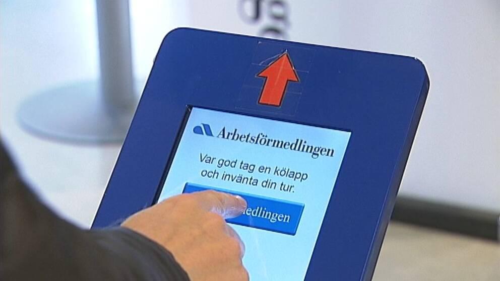 närbild på hand som trycker på en skärm för kölapp på Arbetsförmedlingen