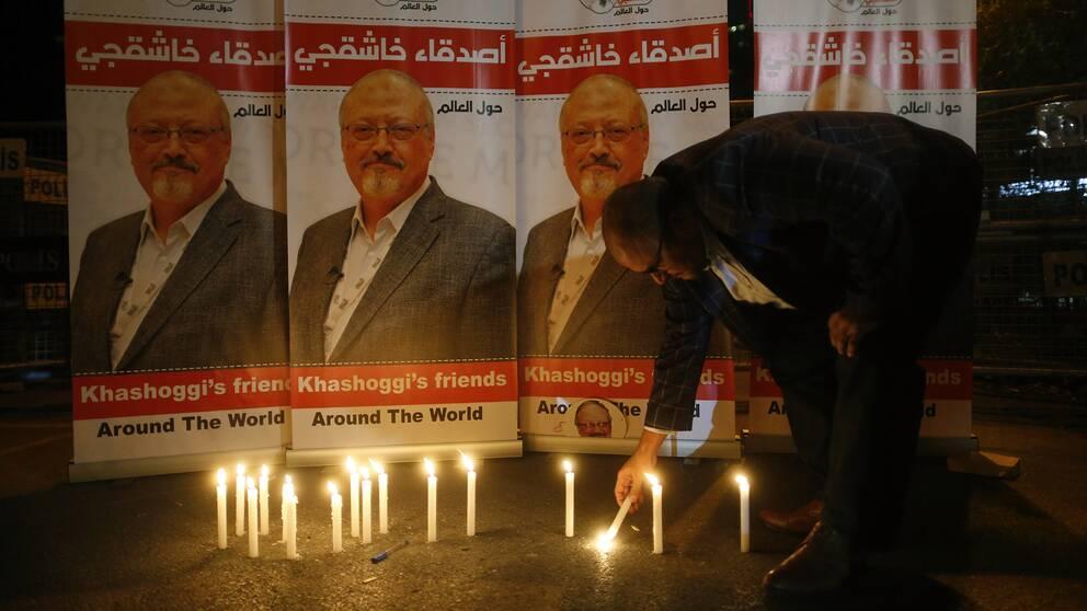 En man tänder ljus framför porträtt av saudiske journalisten Jamal Khashoggi, som misstänks ha mördats.