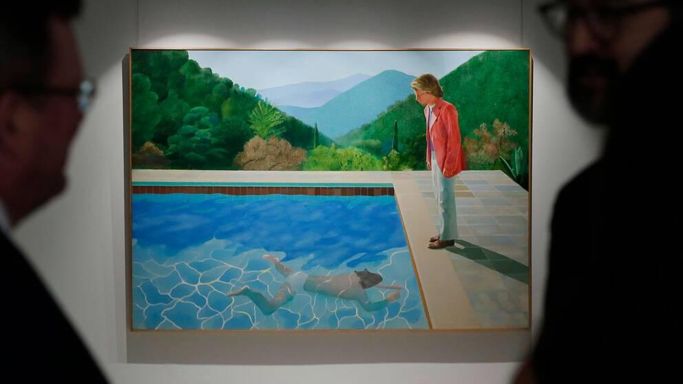 "Besökare betraktar målningen ""Portrait of an artist (pool with two figures)"" inför auktionen i Hong Kong."