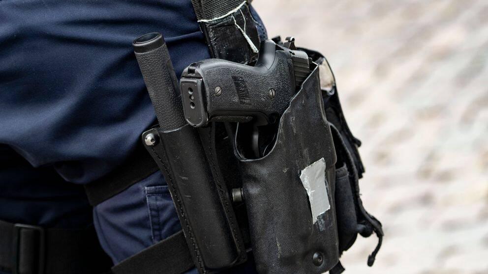 en polis med ett vapen i hölster
