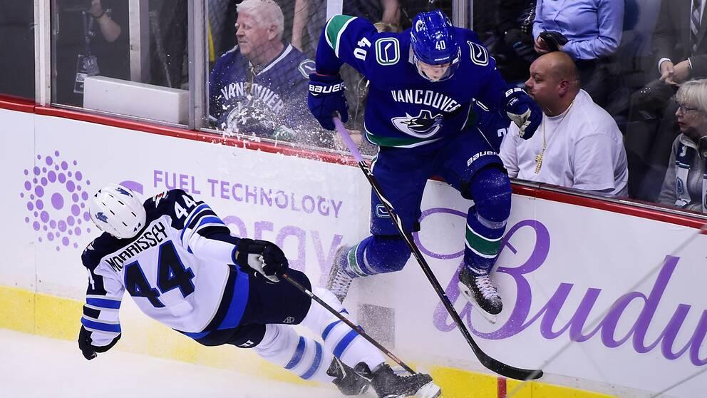 Elias Pettersson, i blått, tacklas av Winnipeg-backen Josh Morrisey.