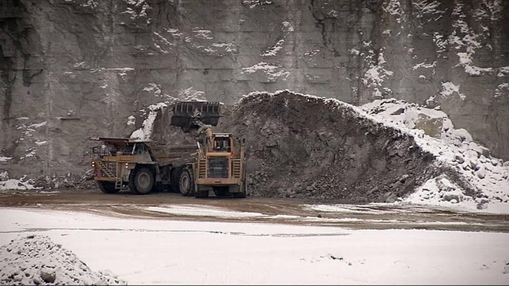 Lastmaskin lastar kalksten på en truck.