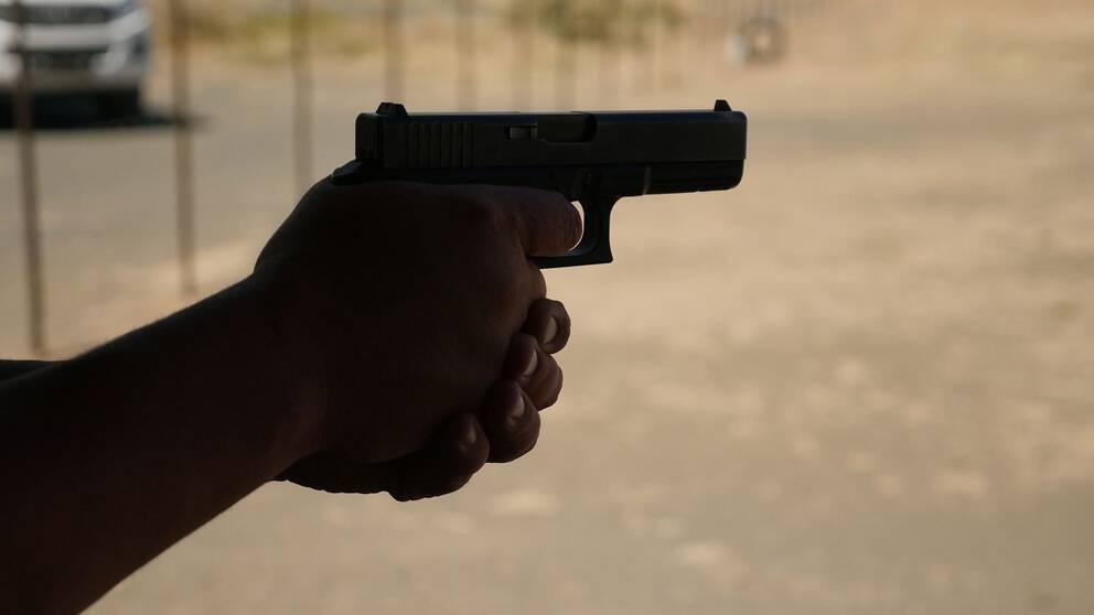 Man som håller i en pistol.