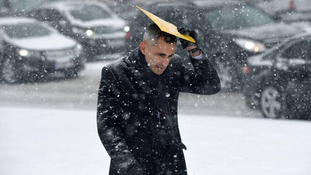 En ukrainsk man skyddar sig från snön när han promenerar genom Kiev. Arkivbild.