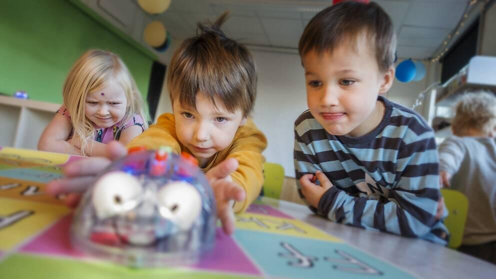 Wilma Verle 5 år, Edwin Åsåker 5 år och Albin Ullström 4 år försöker programmera roboten att gå dit de vill.
