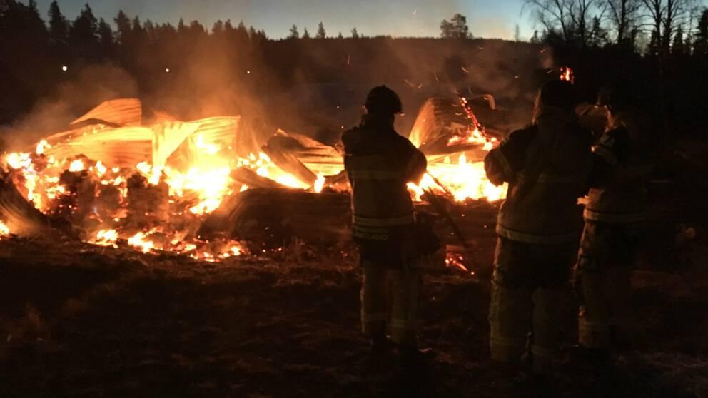 två brandmän syns i silhuett mot brinnade rester av byggnad