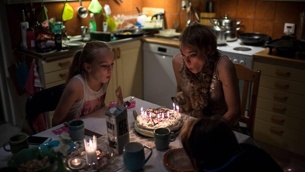 Ida Boström blåser ut ljusen på en tårta.