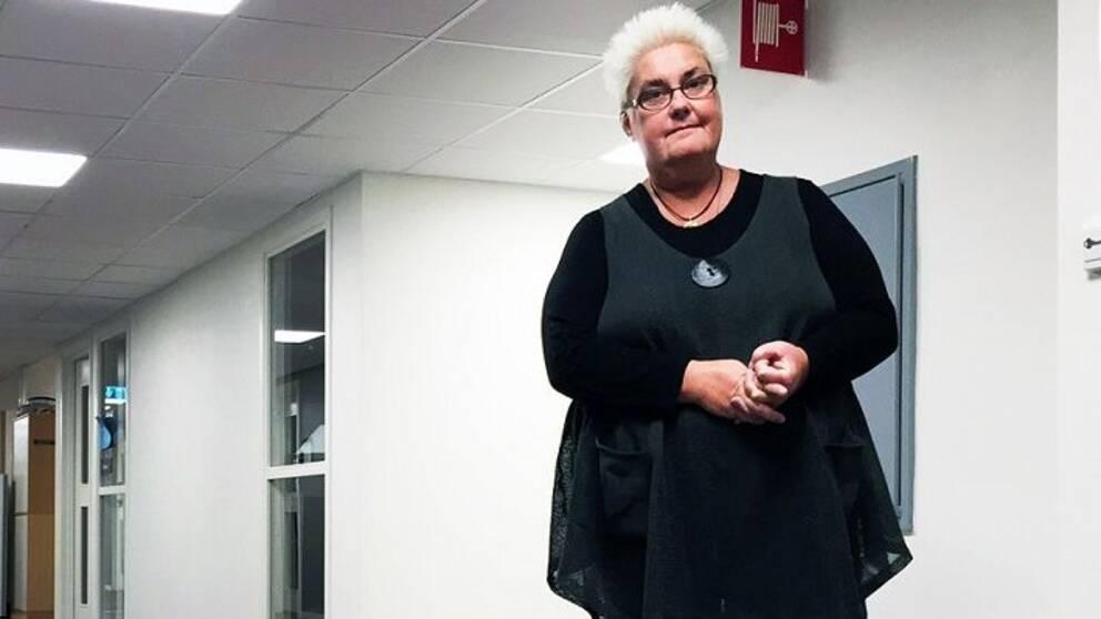 Marie Dahlin står i en korridor med knutna händer