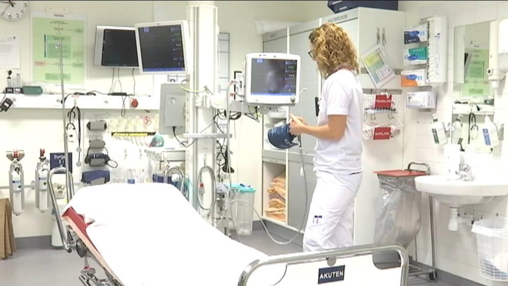 Sjuksköterska i ett undersökningsrum med mycket utrustning.