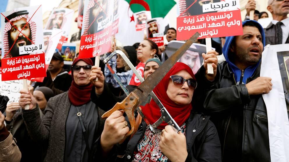 Demonstranter i Tunisien håller upp sågar i protest mot Saudiarabiens kronspring Mohammed bin Salmans besök till landet.