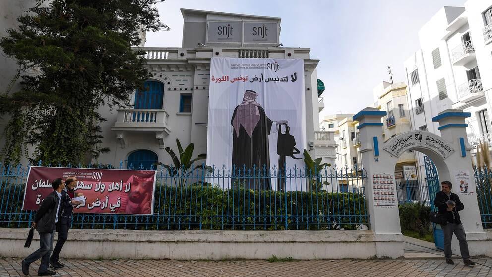 På tunisiska Journalistförbundets fasad hänger en banderoll föreställande Saudiarabiens kronprins, hållandes i en motorsåg.