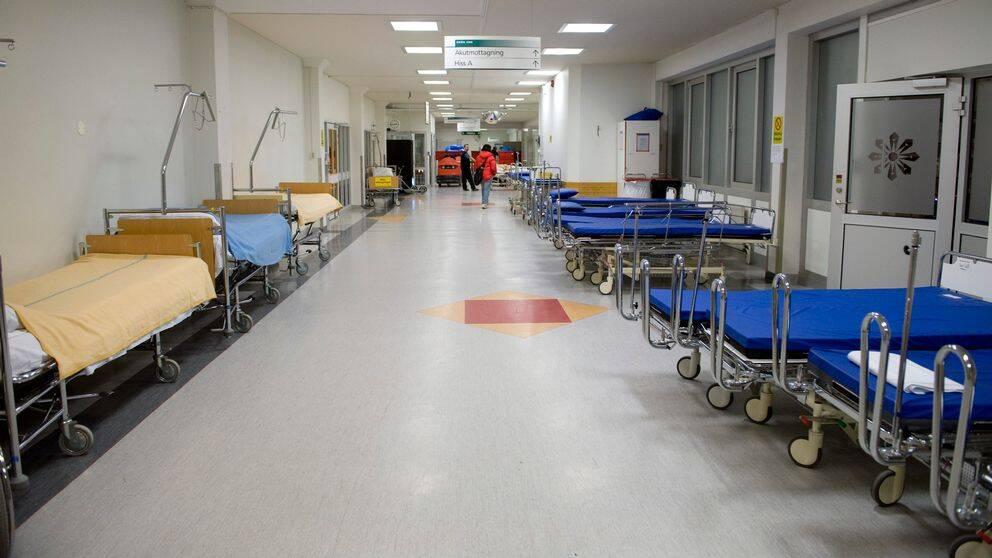 Tomma sjukhussängar i en korridor.