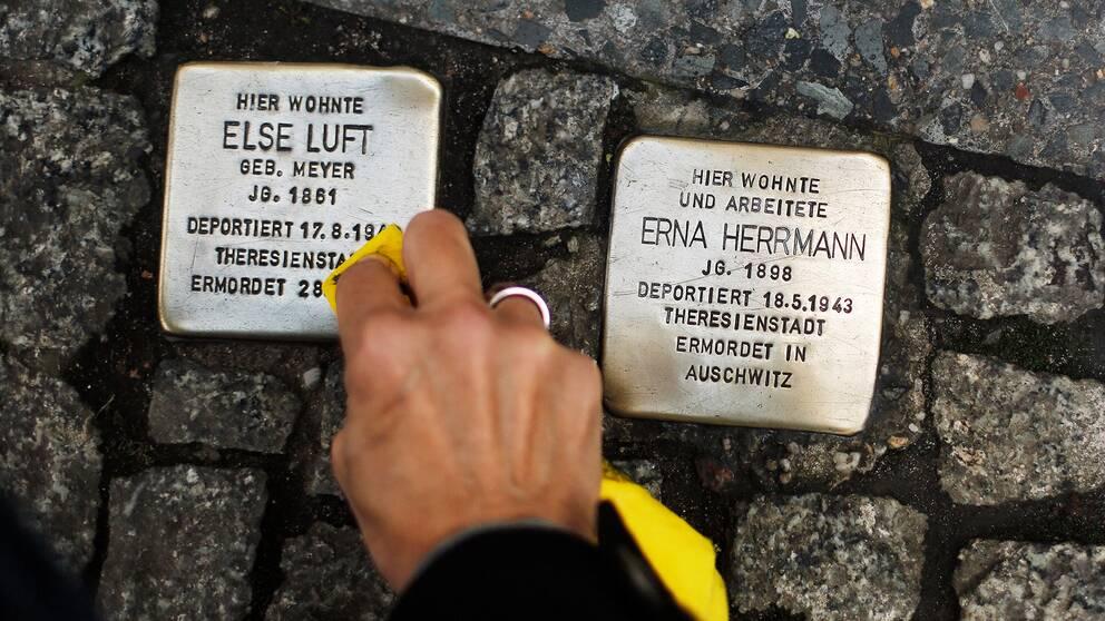 En hand putsar gatustenar till minne av de som dödades under Nazityskland.