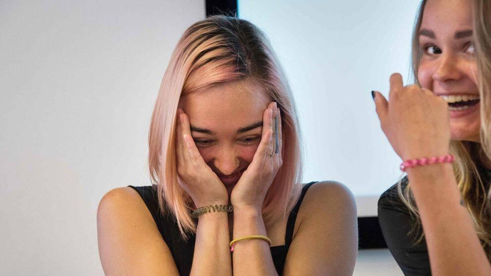 En kvinna som skrattar med händerna för ansiktet.