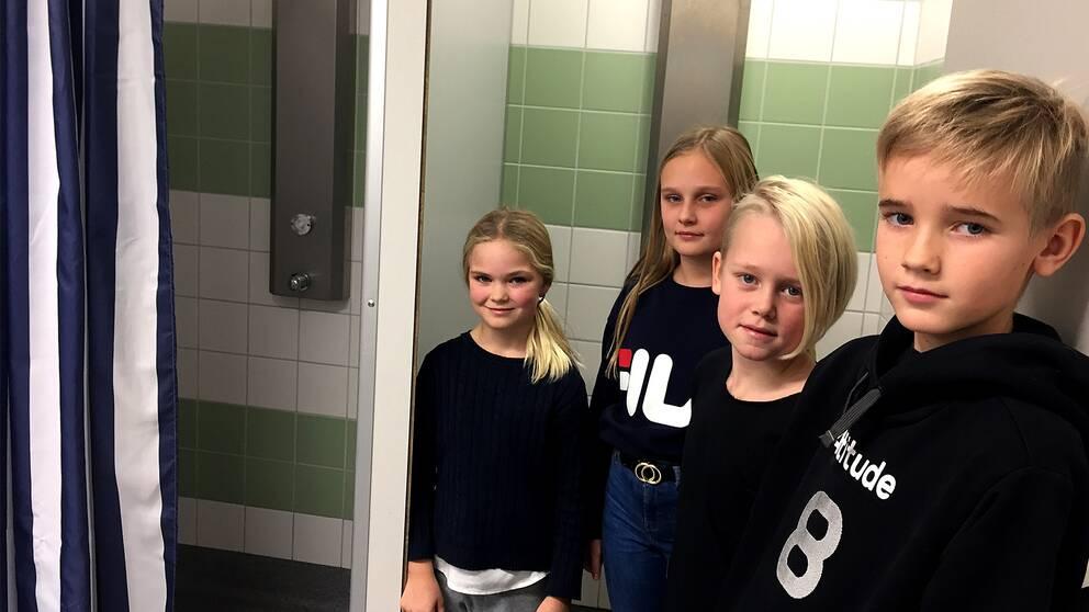 Flera barn står vid dusch med draperi