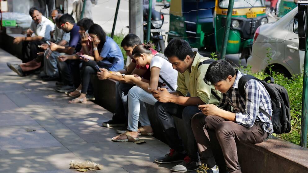 Personer använder sina telefoner i New Delhi