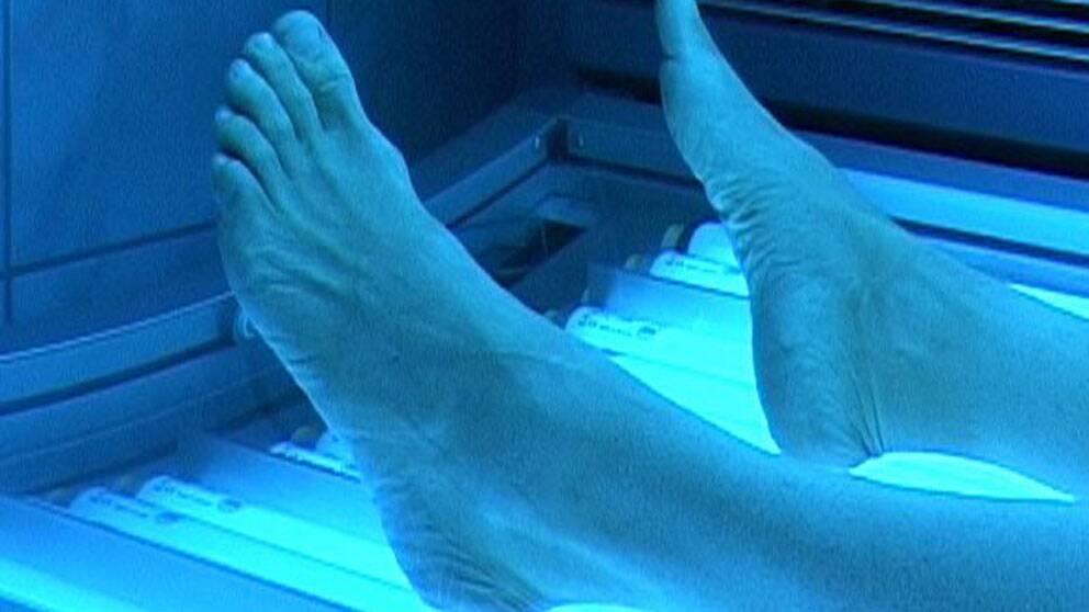 Fötterna på en person som solar solarium.