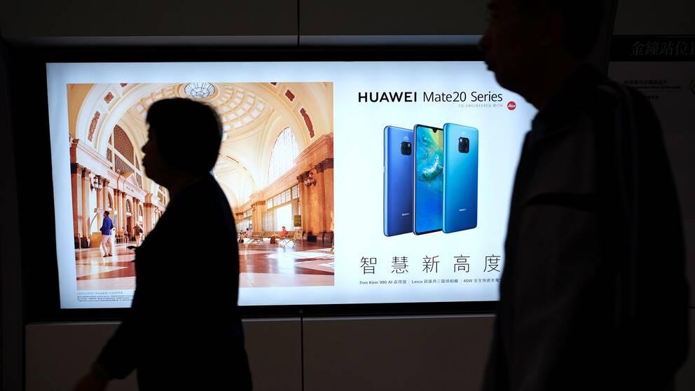 Människor framför reklam för Huawei i Hongkongs tunnelbana