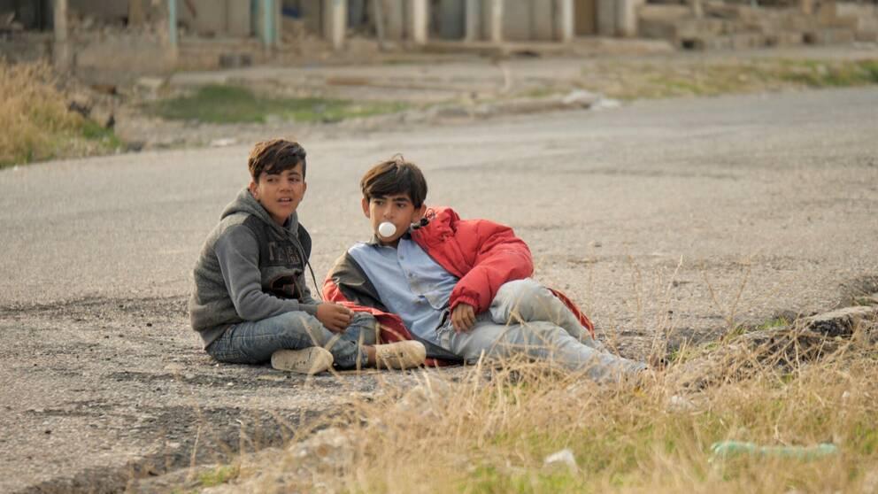 Två pojkar på en öde gata i Sinjar