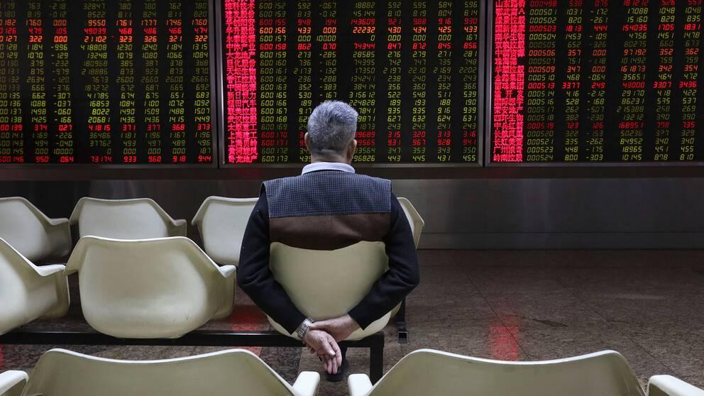 En man tittar på aktiekurser i Peking
