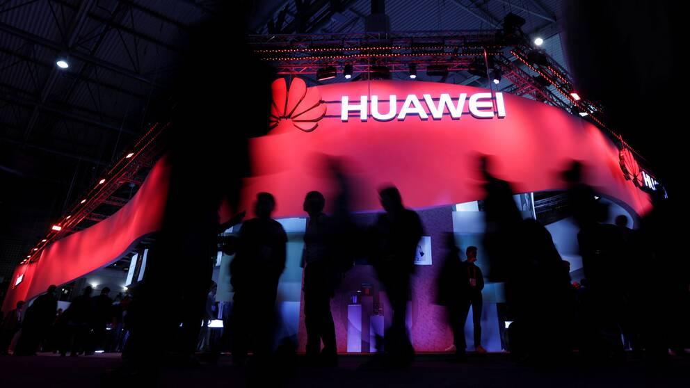 Silhouetter framför en Huawei-monter