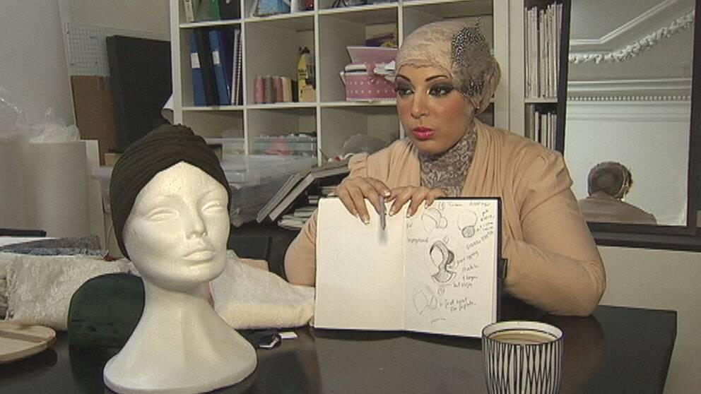 Iman Aldebe som har fått i uppdrag att designa slöjan visar skisserna. Foto:Svt