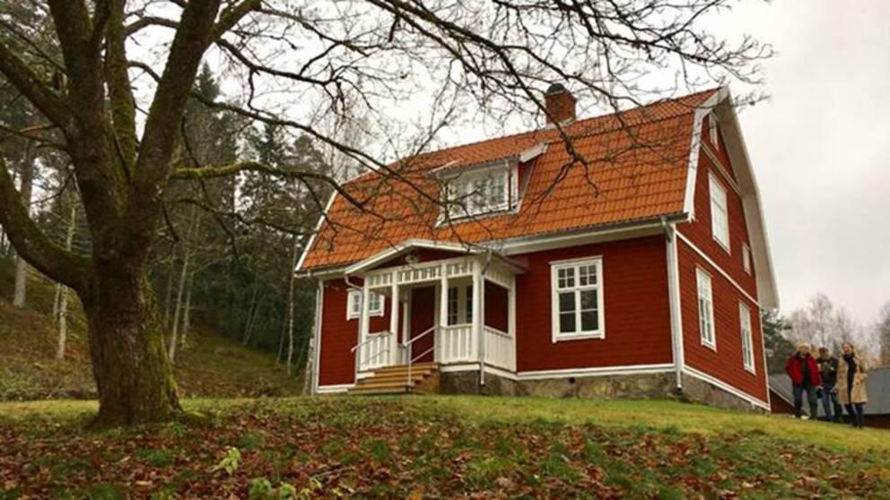 rött trähus med vita knutar