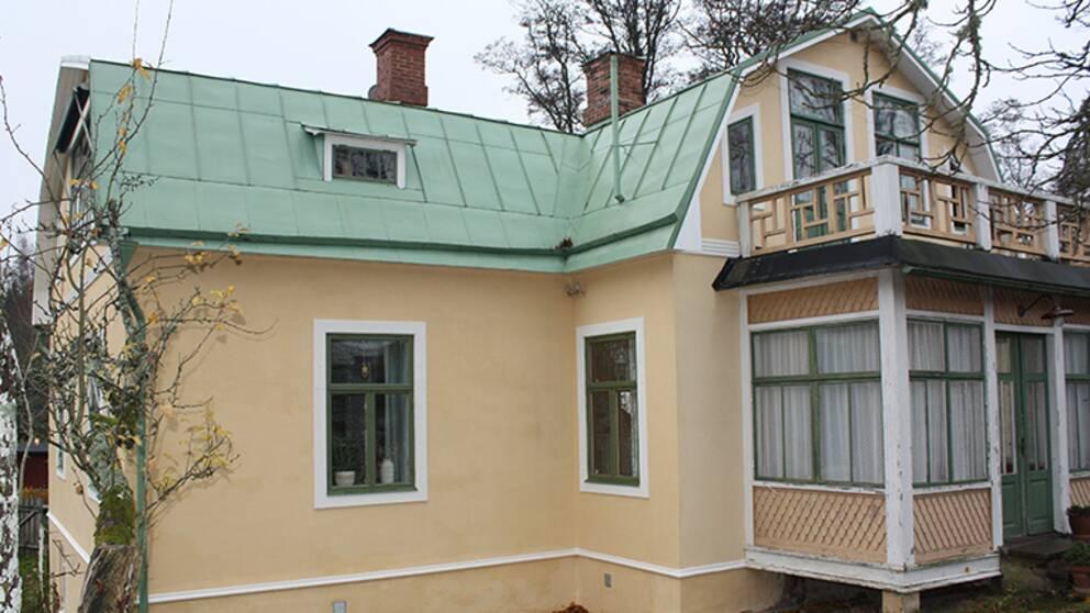 villa med gul rappad fasad och grönt plåttak