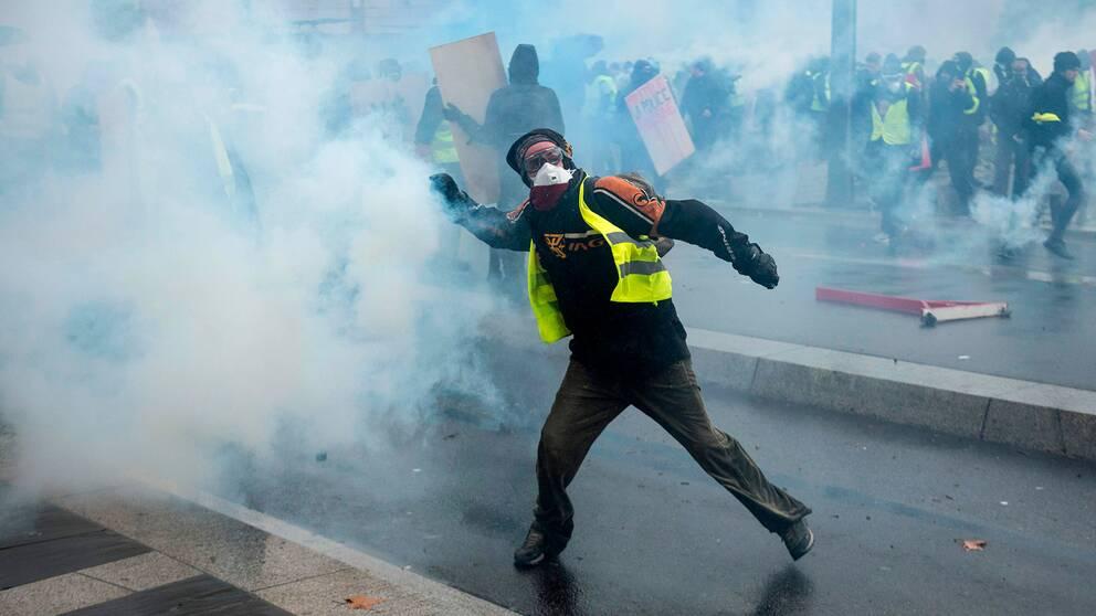 En demonstrant i gul reflexväst kastar tårgas.