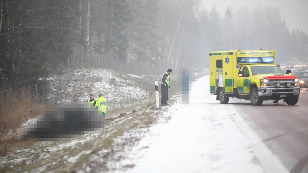 ambulans på vägen, bil i diket, räddningspersonal och en civil person som är blurrad, lite snö på marken
