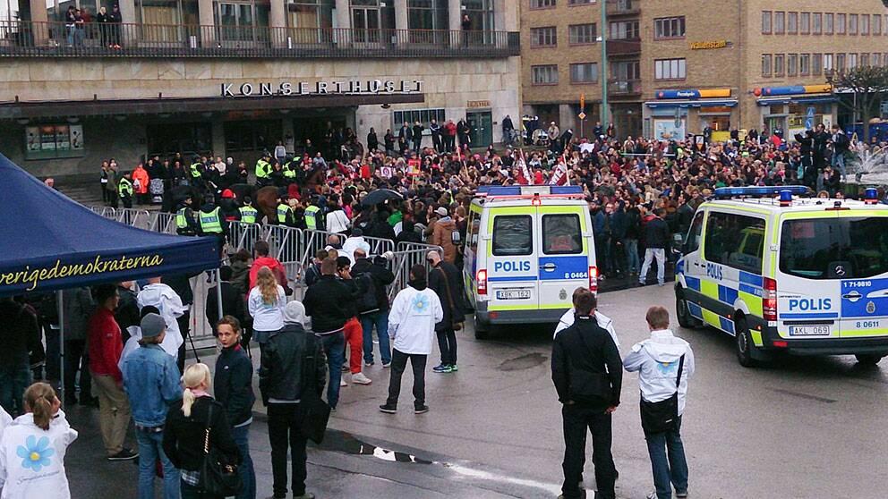Polisen motar bort 100-tals motdemonstranter från Götaplatsen, där SD försöker hålla valmöte med Jimmie Åkesson. Mötet har hindras med talkörer, burop och musikinstrument.