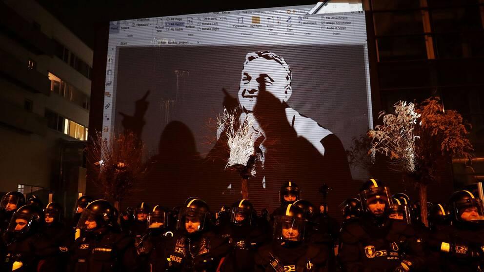 Demonstranter i Budapest projicerar en bild på president Orbán mot tv-husets fasad, som vaktas av kravallpolis.