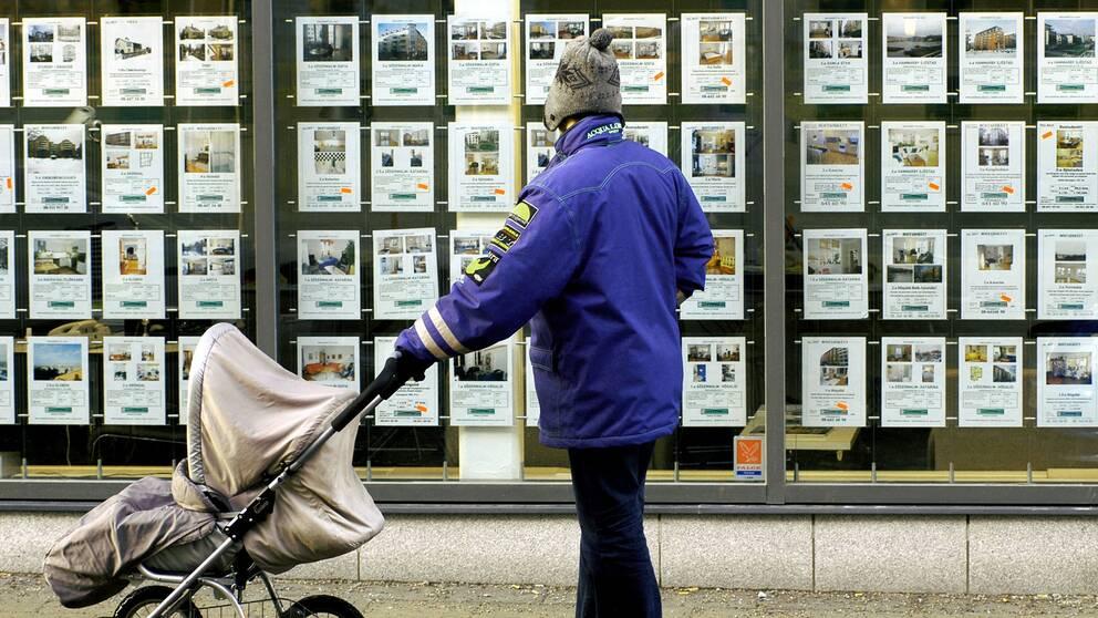 Man med barnvagn tittar på bostadsannonser i skyltfönster.