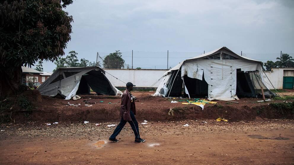 En man passerar tält som förstörts i demonstrationerna i staden Beni i Kongo-Kinshasa.