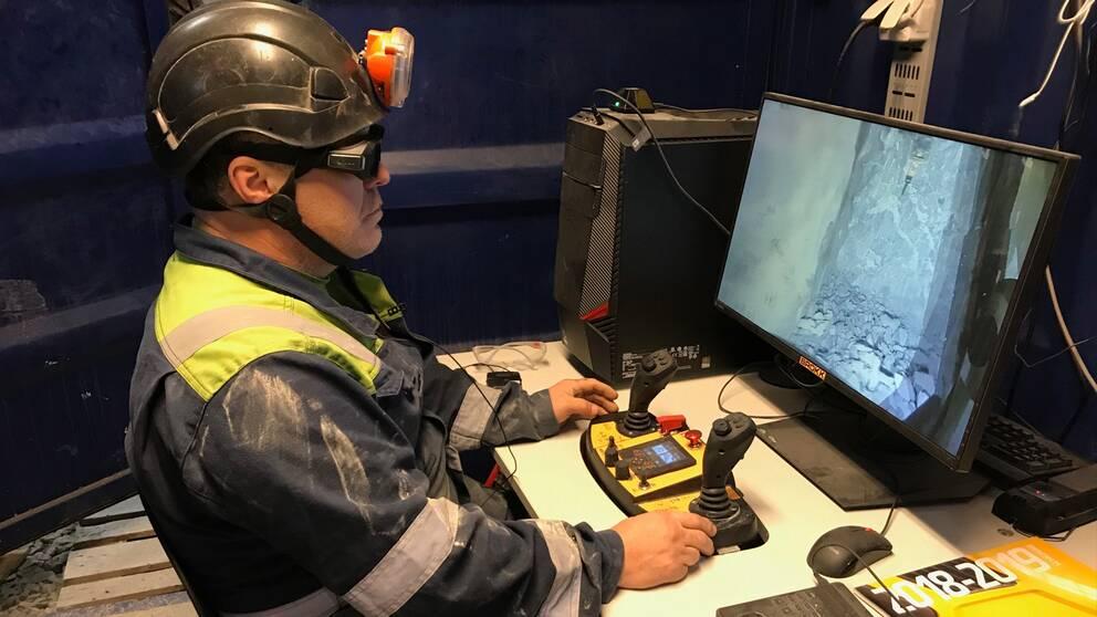 Man sitter vid dator nere i gruva.