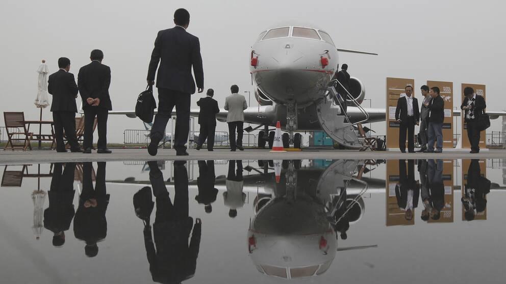 Privatpersoner rör sig mot ett jetplan