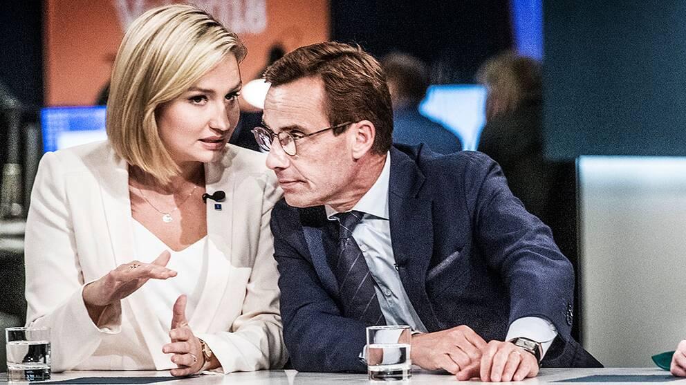Ebba Busch Thor (KD) och Ulf Kristersson (M) viskar till varandra på SVT:s valvaka.