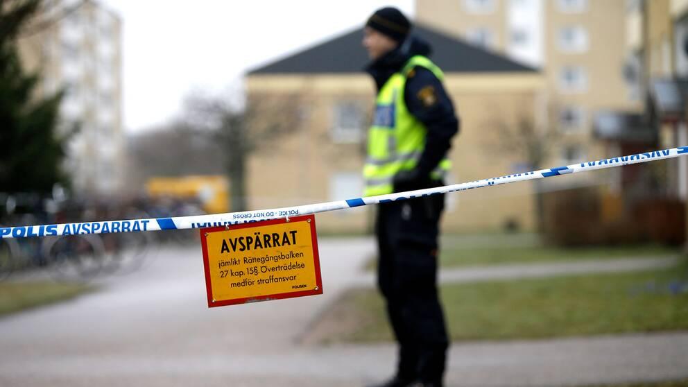 En polis vid en plats där en man sköts till döds av polis
