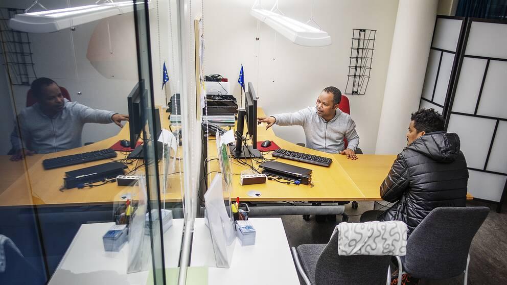 Awet Mebratu jobbar i en av kommunens receptioner och hjälper här en besökare att hitta rätt på Försäkringskassans webbsida.