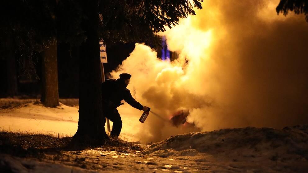 kvällstid vinter, polisman som sprutar med brandsläckare på kraftigt rykande bil
