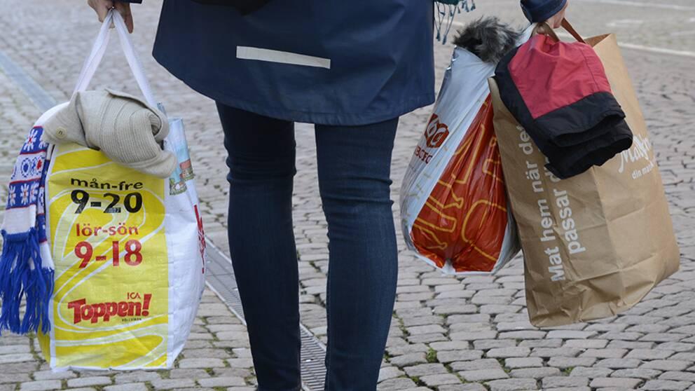 En kvinna går med kläder till insamlingen samt en massa skor i en behållare.