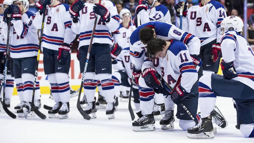 USA:s Ryan Poehling, på knä, deppar efter finalförlusten mot Finland. Målskytten Alexander Tjmelevski är framme och tröstar.