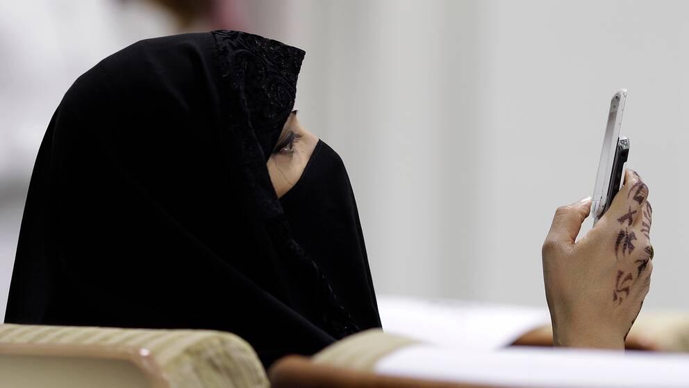 En kvinna i niqab tittar i sin mobil.