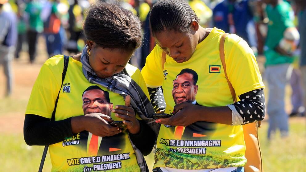 Kvinnor i Harare i Zimbabwe kollar efter information i sina mobiler inför fjolårets val