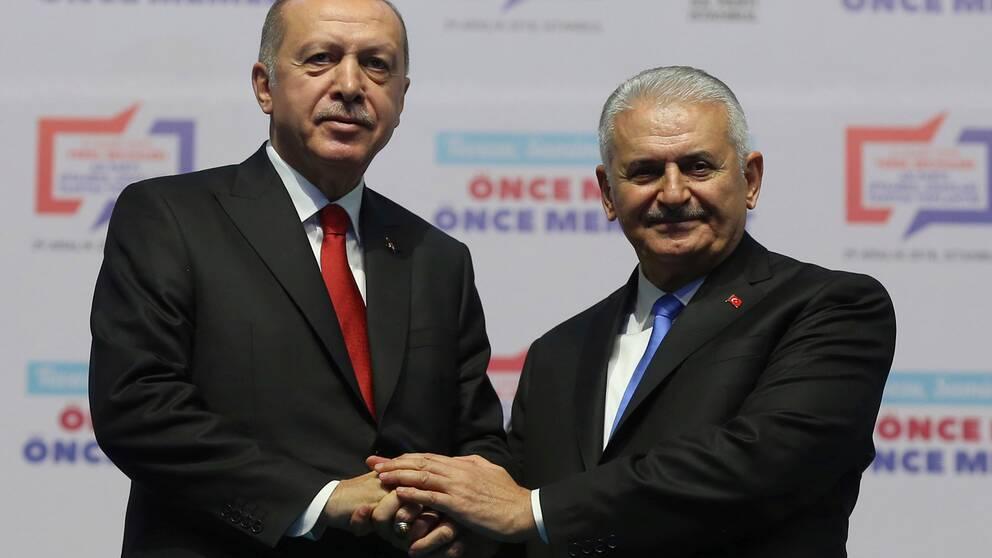 Turkiets president Recep Tayyip Erdogan, till vänster, skakar hand med Binali Yildirim, tidigare premiärminist