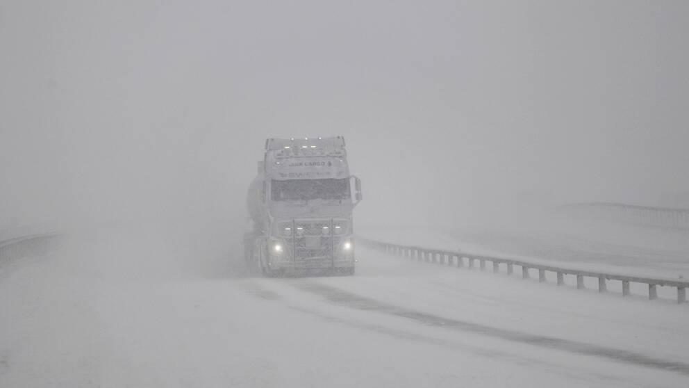 Vit lastbil kör i snöstorm.